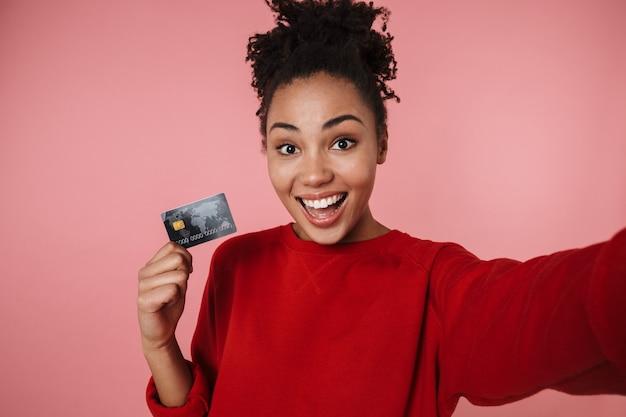 Красивая удивительная счастливая возбужденная молодая африканская женщина позирует изолированной над розовой стеной, принимая селфи камерой с помощью кредитной карты.