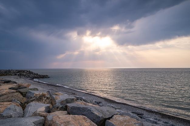 Красивые удивительные великолепные пейзажи скалистого берега, моря и пасмурного угрюмого неба с солнечными лучами