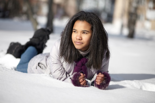 Beautiful american black female lying in the snow outdoors
