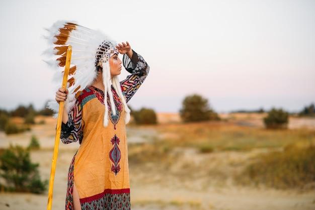 ネイティブの衣装を着た美しいアメリカインディアンの女の子は、屋外で遠くに見えます。野鳥の羽でできた頭飾り。チェロキー、ナバホ文化、民族