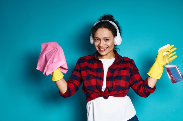 掃除のぼろきれとスプレーを保持している美しいアメリカ人女性、青の上に立っている歯を見せる笑顔で笑顔