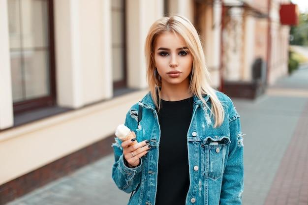 Красивая американская женщина в винтажной джинсовой одежде с мороженым в солнечный летний день
