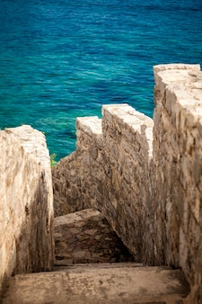 Beautiful ancient stone wall with stairs leading to blue sea