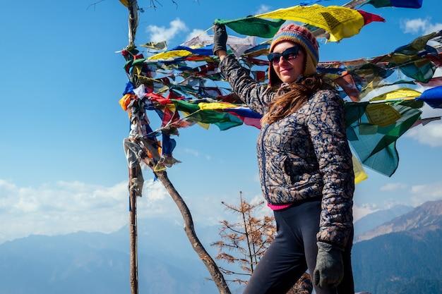 美しくアクティブな女性は、山でのトレッキングで休んでいます。山でのアクティブなレクリエーションと観光の概念。ネパールヒマラヤでのトレッキング