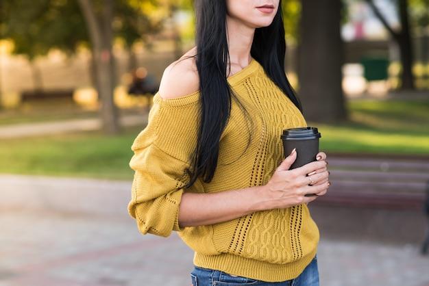 Красивая и привлекательная кавказская девушка брюнет в желтом свитере с чашкой кофе позирует во время прогулки по городу.