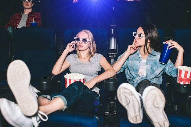美しく魅力的な女の子が椅子に座っています。ブロンドの女の子が電話で話しています。彼女の友人は沈黙のシンボルを見せています。彼女は静かになり、映画を見ている間話をやめたいと思っています。