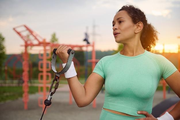 静止した屋外ケーブルクロスオーバーで上腕二頭筋の運動をしているヒスパニック民族の美しく魅力的なスポーティーな女性。スポーツグラウンドで運動するアスリートを決定する