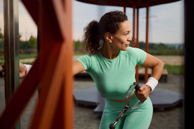 静止した屋外ケーブルクロスオーバーで上腕三頭筋と肩の筋肉の運動をしているラテンアメリカ民族の美しく魅力的な女性。スポーツグラウンドで運動するアスリートを決定する