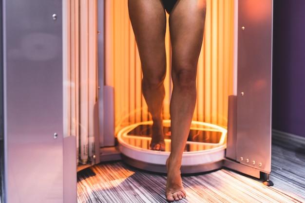 일광욕실에서 선탠을 하는 아름답고 매력적인 젊은 여성.