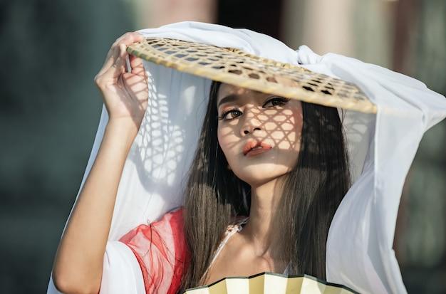 아름답고 호전적인 얼굴; 중국 복장에서 아시아 당신 여자입니다.
