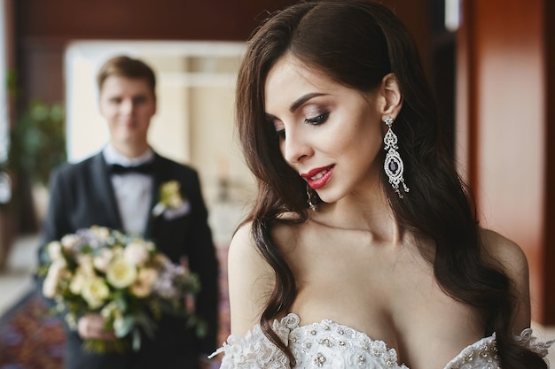 Красивая и грудастая брюнетка-модель с ярким макияжем и сексуальным телом в модном длинном платье с соблазнительным декольте и в роскошных серьгах с бриллиантами улыбается и позирует в интерьере