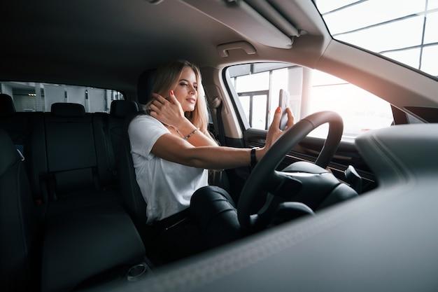 Красиво и очаровательно. девушка в современной машине в салоне. днем в помещении. покупка нового автомобиля.