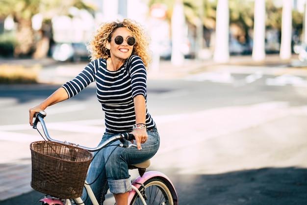 美しく陽気な大人の若い女性は、街の日当たりの良い都会のアウトドアレジャー活動で自転車に乗ることを楽しんでいます-幸せな人々の肖像画-楽しんで外でトレンディな女性