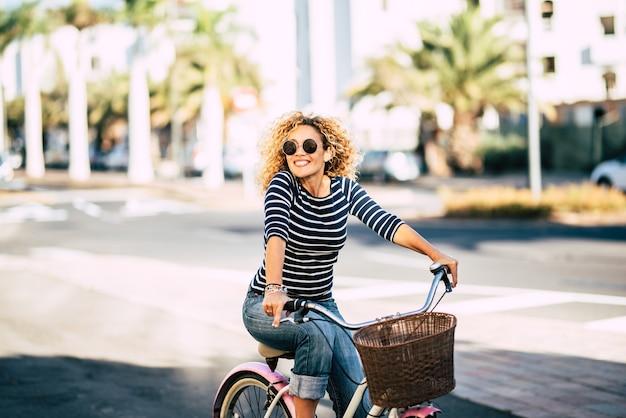 美しく陽気な大人の若い女性は、街の日当たりの良い都市の屋外レジャー活動で自転車に乗ることをお楽しみください