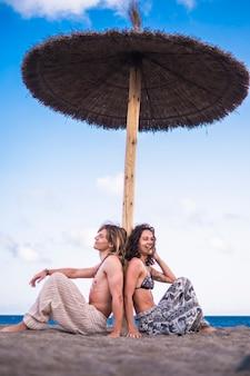 Красивая и веселая кавказская молодая пара мужчина женщина сидит под солнцем зонтика на пляже, наслаждаясь отдыхом и летним отдыхом на свежем воздухе