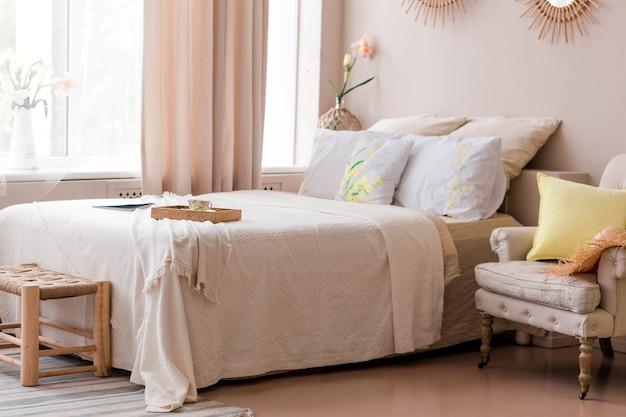 베이지 색상의 아름답고 편안한 침실. 침실에는 현대적인 침대, 안락 의자 및 침대 옆 스탠드가 있습니다. 가로 사진