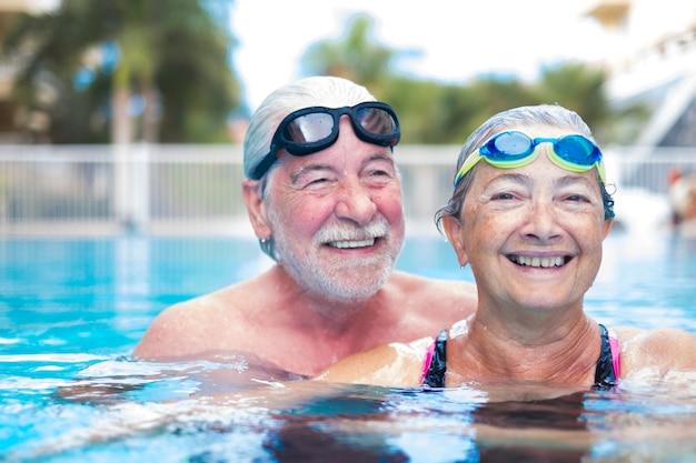 아름답고 귀여운 수영장에서 두 명의 노인이 함께 즐거운 시간을 보내고 있습니다 - 피트니스 및 건강한 생활 방식 - 여름에는 함께