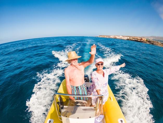 바다 한가운데에 있는 아름답고 귀여운 노부부나 노부부가 작은 배를 타고 새로운 곳을 발견하고 있습니다. 전화를 들고 남편과 셀카를 찍는 성숙한 여성
