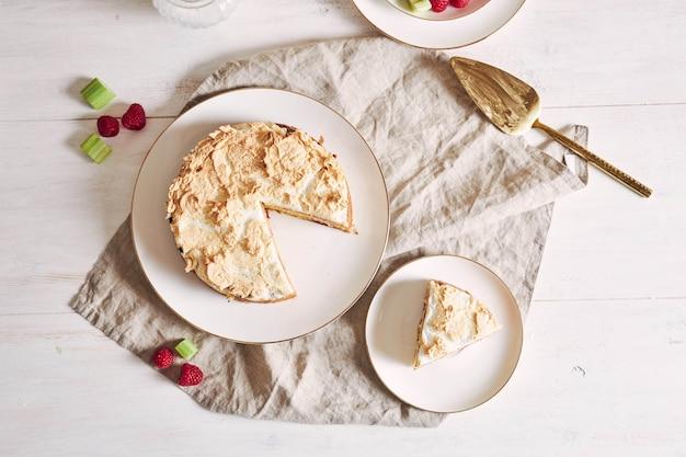 テーブルの上に材料が入った美しくておいしいラズベリーとルバーブのケーキ