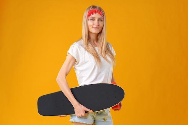 Красивый и модный подросток позирует со скейтбордом в студии