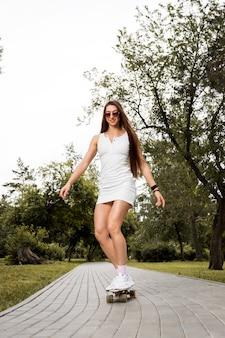 スケートボードでポーズをとって美しく、ファッションの若い女性。スポーツ活動のライフスタイルの概念