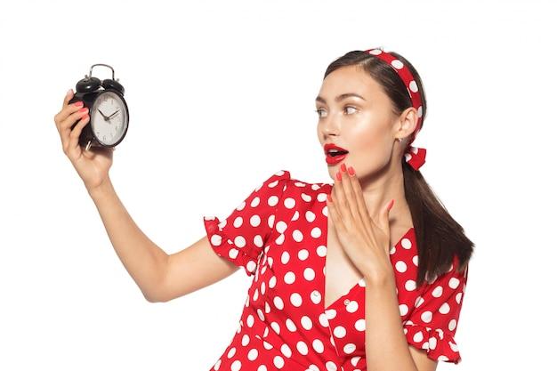 시계를 들고 핀 업 모양으로 아름답고 패션 젊은 여자
