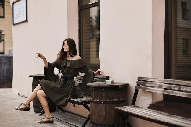 Красивая и модная брюнетка модель девушка в стильном платье с обнаженными плечами сидит на скамейке и позирует на улице на маленькой городской улице