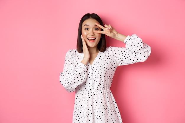 아름 답 고 여성 아시아 여자 눈에 귀여운 기호를 표시 하 고 핑크 드레스에 서 서 카메라에 놀 랐 다.