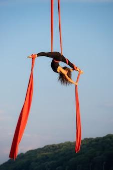 하늘 배경에 공중 실크와 함께 춤을 아름답고 유연한 여성 서커스 아티스트.