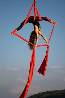 하늘에 공중 실크로 춤을 추는 아름답고 유연한 여성 서커스 아티스트.