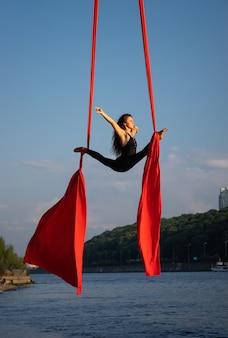 하늘과 강 해안선이있는 공중 실크로 춤을 추는 아름답고 유연한 여성 서커스 아티스트