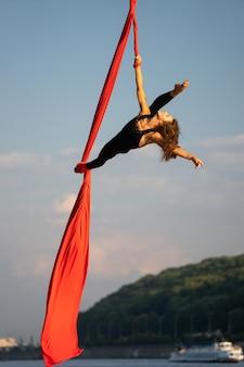 Красивая и гибкая цирковая артистка танцует воздушным шелком с небом и береговой линией реки