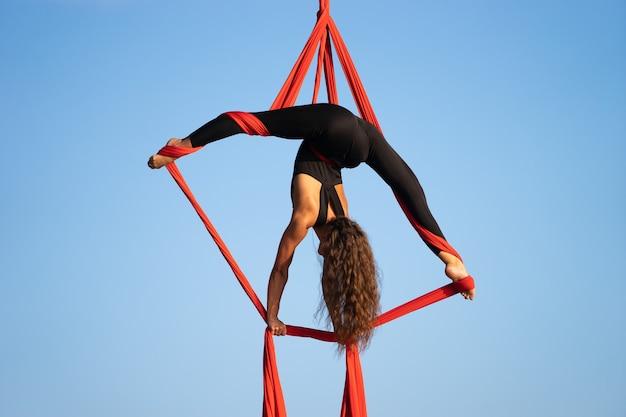 Красивая и гибкая цирковая артистка танцует с воздушным шелком