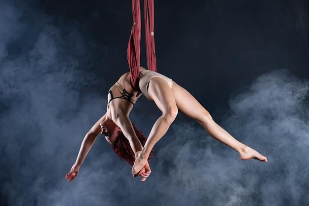 공중 실크로 춤추는 아름답고 유연한 여성 서커스 아티스트