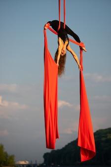 공중 실크로 춤을 추는 아름답고 유연한 여성 서커스 아티스트.