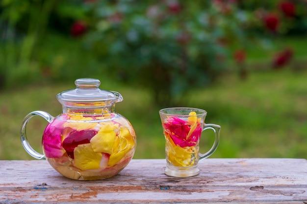 ガラスのティーポットに黄色、ピンク、赤の花びらのバラ、木製のテーブルのサマーガーデンにあるマグカップからの美しく香りのよいお茶。自然の背景にバラの花びらからハーブの花茶をクローズアップ