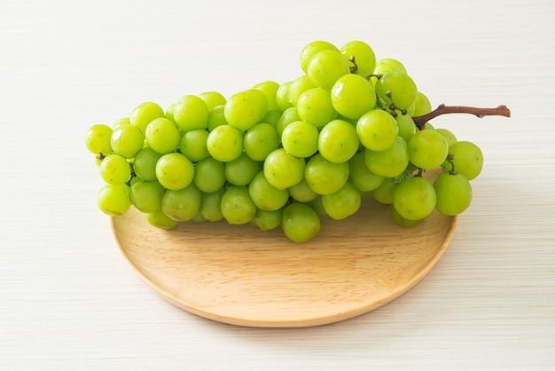 木の板の美しくて新鮮な緑のブドウ