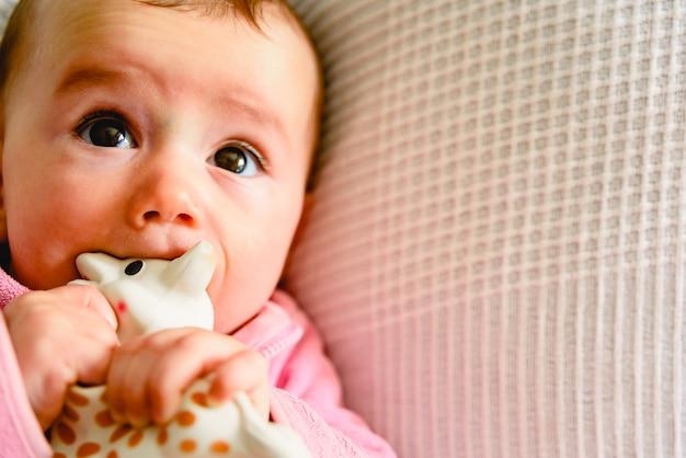 아름답고 친절한 6 개월 된 여자 아기가 고통과 고통을 진정시키기 위해 물고