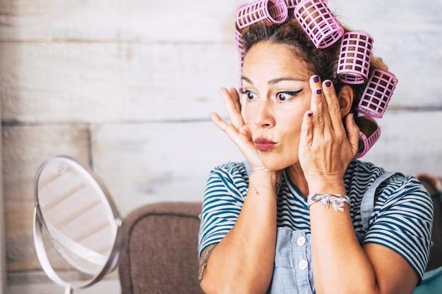 Красивое и забавное выражение кавказской взрослой женщины готовится дома перед зеркалом с макияжем на лице - проверка морщин и старение концепции для молодых людей - бигуди на волосах