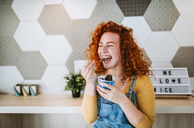 おいしい手作りアイスクリームを食べるのを楽しんでいる美しくて幸せな茶色の髪の女性。