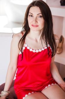 Красивая и счастливая брюнетка в красной пижаме или сорочке позирует в своей спальне