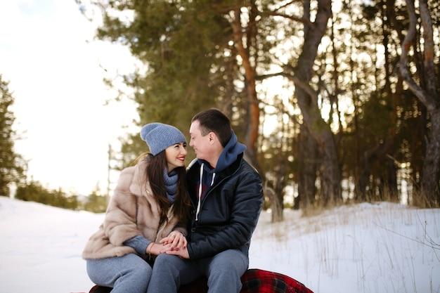 雪に覆われた森の冬に毛布の上に座って恋に美しい幸せなカップル