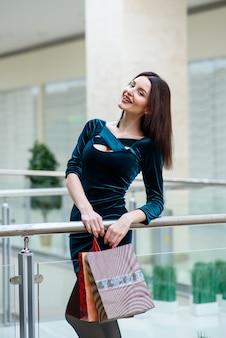 Красивая и счастливая девушка делает покупки в торговом центре