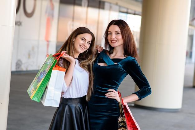 美しくて幸せな女の子がショッピングモールで買い物をしています。
