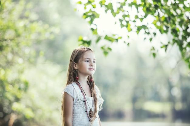 히피 스타일의 밝고 화창한 날의 자연에 있는 아름답고 행복한 어린 소녀