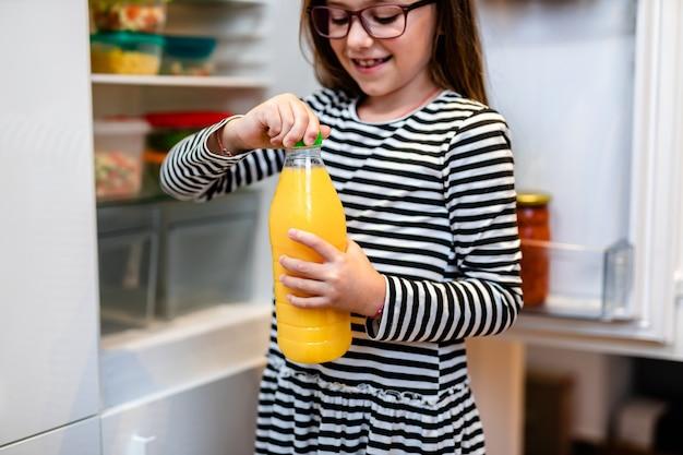 냉장고에서 신선한 오렌지 주스 한 병을 복용하는 아름답고 행복한 어린 소녀.