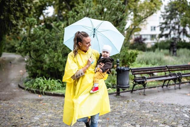 雨の日に都市公園を歩いている彼女の赤ちゃんと美しくて幸せな中年女性。