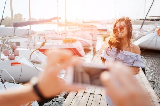 Красивая и счастливая модель стоит и позирует. она улыбается. ветер развевает ее волосы. молодая женщина носит солнцезащитные очки