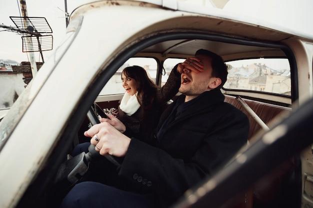 美しくて幸せな女性と男が車に座る