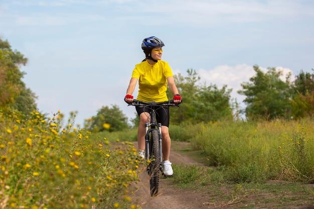 아름답고 행복한 여성 자전거 타는 사람은 자연 속에서 자전거를 탄다. 건강한 라이프 스타일과 스포츠. 여가와 취미